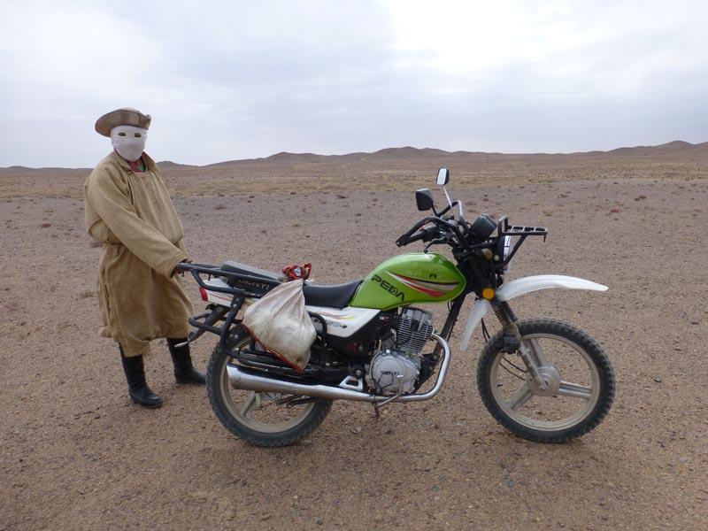 Motorradfahrer mit Gesichsmaske in der Wüste Gobi
